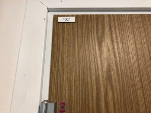 Bilden visar det övre vänstra hörnet av ytterdörren, sett utifrån. Där finns en liten bricka monterad som visar det unika lägenhetsnumret